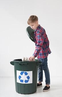 Adorable jeune garçon heureux de recycler