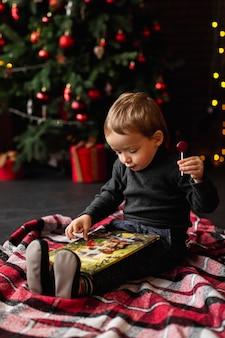 Adorable jeune garçon jouant avec des jouets de noël