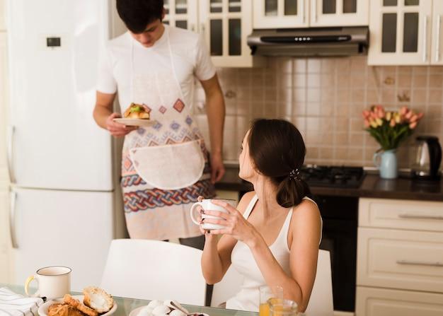 Adorable jeune homme prépare le petit déjeuner pour sa petite amie