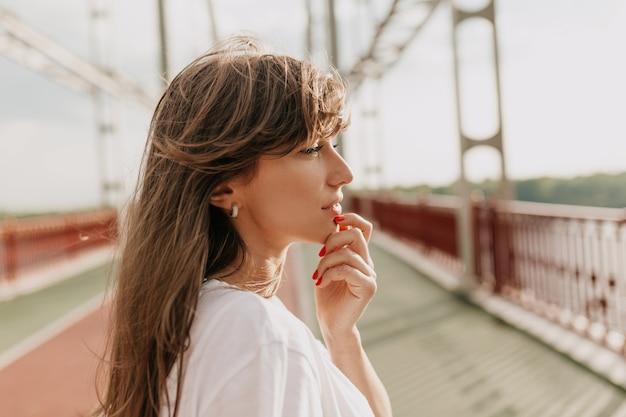 Adorable jolie femme aux cheveux châtain clair sur un pont
