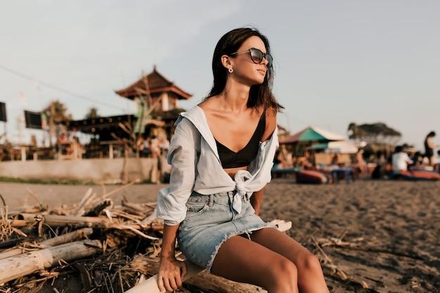 Adorable jolie fille aux cheveux courts foncés en jupe et chemise bleue assise sur une plage de sable au soleil