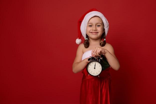Adorable jolie petite fille vêtue d'un costume de carnaval de santa pose avec un réveil avec minuit sur l'horloge du visage, regardant la caméra, sur fond de couleur rouge avec espace de copie pour l'annonce de noël