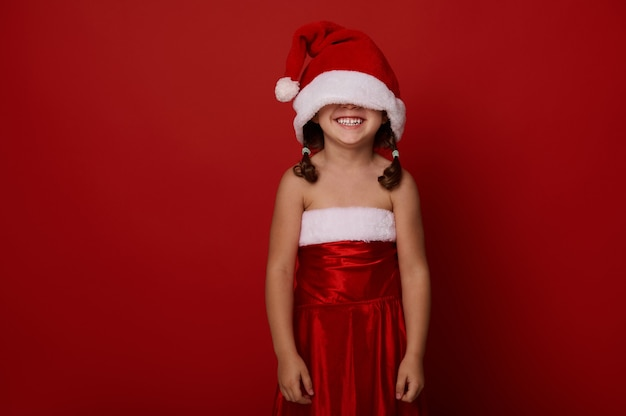 Adorable magnifique petite fille de 4 ans, enfant mignon dans des vêtements de père noël et un chapeau couvrant ses yeux, sourit à pleines dents posant sur fond rouge avec espace de copie pour l'annonce de noël et du nouvel an