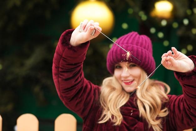 Adorable mannequin blonde tenant des feux de bengale brillants à l'arbre de noël principal de kiev. effet de flou