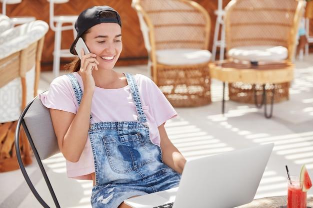 Adorable modèle féminin heureux recrée dans un restaurant confortable avec un ordinateur portable
