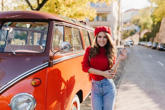 Adorable modèle féminin avec manucure noire posant sur la route avec un sourire charmant en chaude journée d'automne