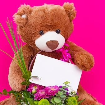 Adorable ours en peluche brun drôle tenant une carte de papier vierge blanche