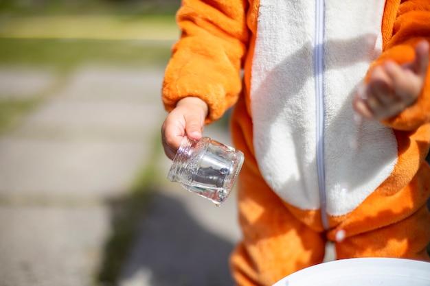 Adorable petit bambin jouant avec de l'eau dans la cour au soleil. enfant en costume de renard