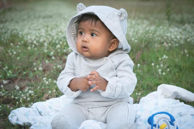 Adorable petit bébé asina assis au jardin de fleurs blanches