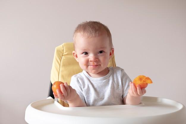 Adorable petit bébé assis dans une chaise haute et tenant des fruits d'abricot dans les deux mains bébé nourrissant la nutrition de l'enfant