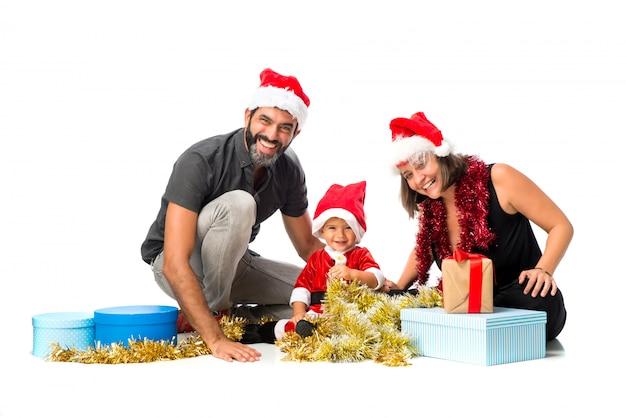 Adorable petit bébé avec ses parents à des fêtes de noël sur fond blanc isolé