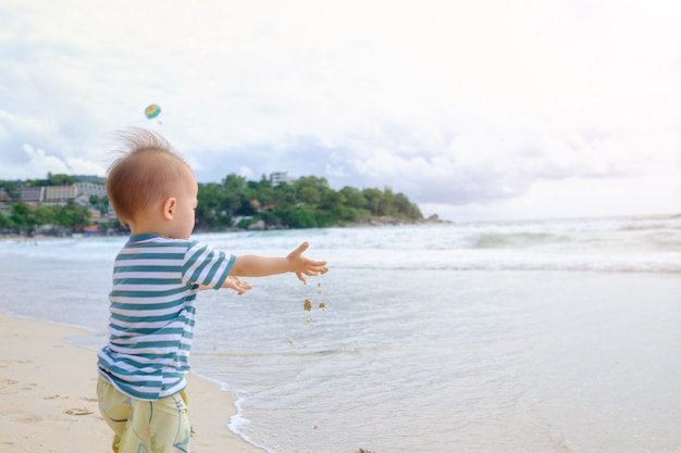 Adorable petit enfant de bébé garçon asiatique sur la plage avec des mains sales recouvert de sable mouillé