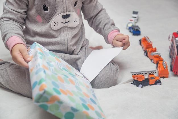 Adorable petit enfant déballe les cadeaux assis sur le lit