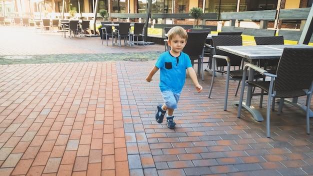 Adorable petit garçon de 3 ans courant sur une petite rue de la ville européenne