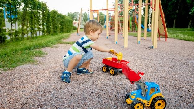 Adorable petit garçon de 3 ans jouant avec du sable et vous camion et remorque dans le parc
