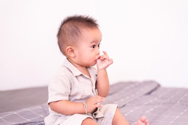 Adorable petit garçon asiatique suçant le pouce alors qu'il était assis dans la chambre, joyeux nouveau-né