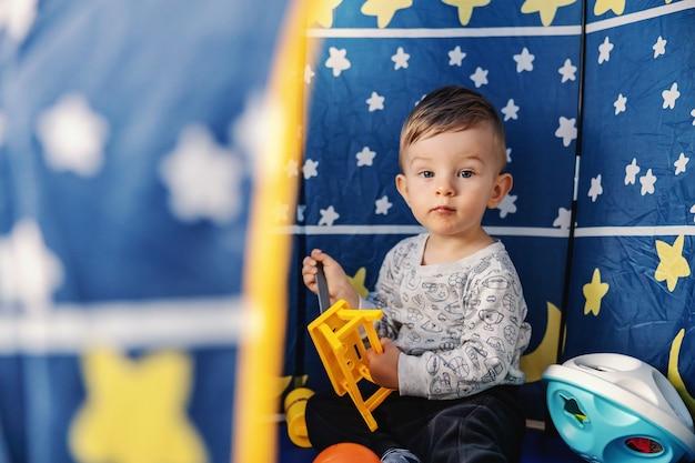 Adorable petit garçon assis dans sa tente à la maison et jouant avec des jouets.