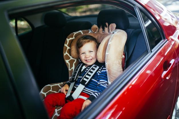 Adorable petit garçon assis dans un siège auto.