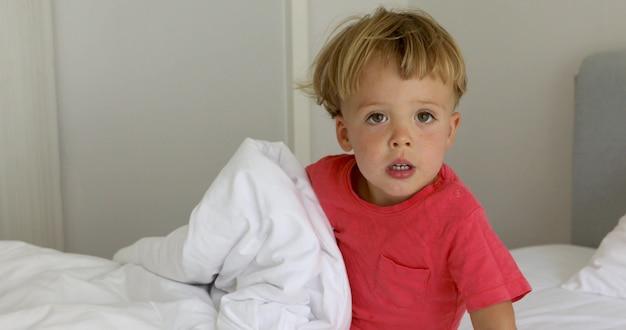 Adorable petit garçon assis sur un lit avec des draps blancs à la recherche de suite
