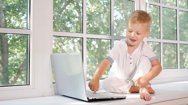 Adorable petit garçon assis sur le rebord de la grande fenêtre blanche dans un ordinateur portable