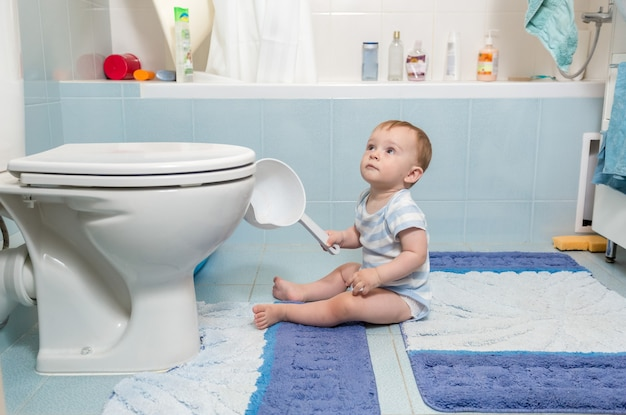 Adorable petit garçon assis sur le sol dans la salle de bain