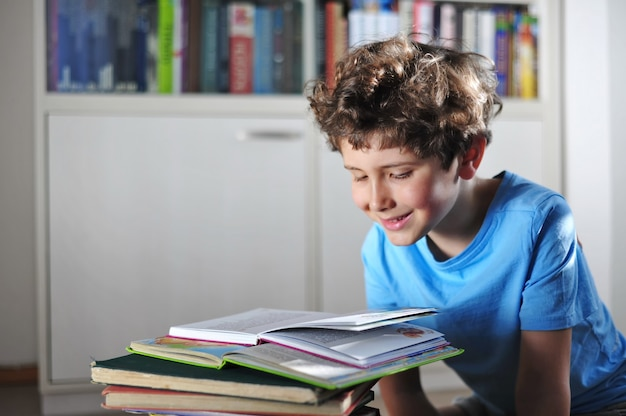 Adorable petit garçon aux cheveux bouclés lit un livre fascinant, drôle et intéressant et sourit