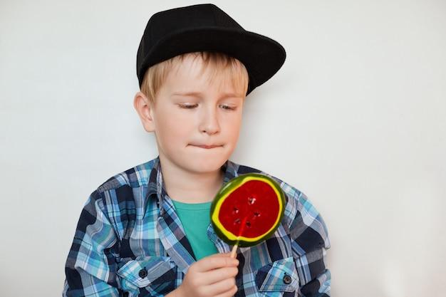 Adorable petit garçon en chemise tendance et casquette noire regardant une grosse sucette colorée. écolier mignon portant à la mode