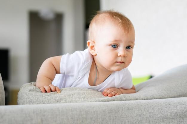 Adorable petit garçon dans une chambre blanche et ensoleillée. nouveau-né se détendre sur un lit bleu. garderie pour les jeunes enfants.