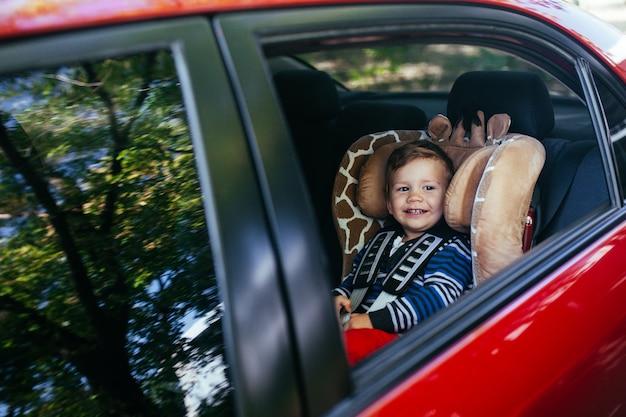 Adorable petit garçon dans le siège auto de sécurité.