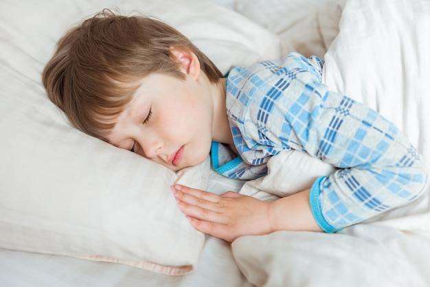 Adorable petit garçon endormi dans son lit