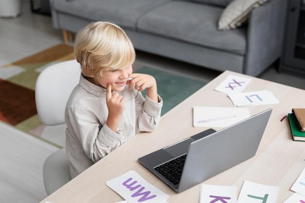 Adorable petit garçon faisant une séance d'orthophonie en ligne