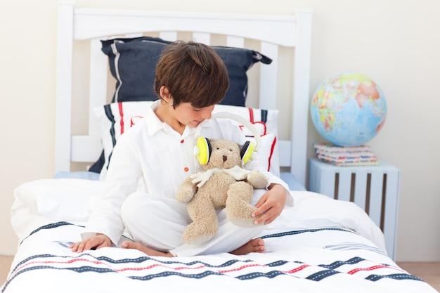 Adorable petit garçon jouant avec un ours en peluche