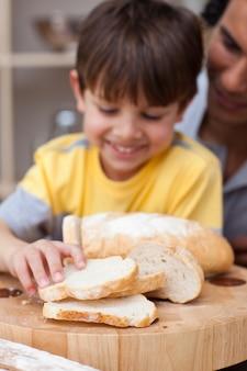 Adorable petit garçon, manger du pain avec son père