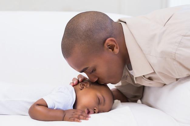 Adorable petit garçon qui dort tout en étant surveillé par son père