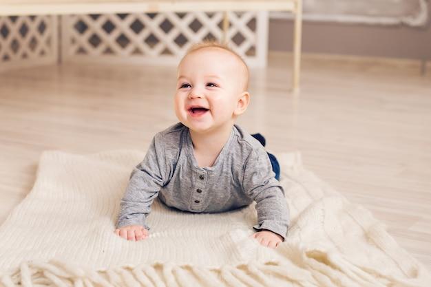 Adorable petit garçon riant dans une chambre ensoleillée blanche. nouveau-né relaxant. matinée familiale à la maison.