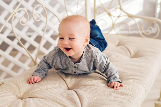 Adorable petit garçon riant dans une chambre ensoleillée. nouveau-né relaxant. crèche pour jeunes enfants. matinée familiale à la maison