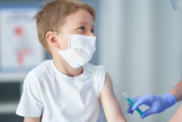 Adorable petit garçon se faisant vacciner au cabinet du médecin