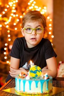 Adorable petit garçon de sept huit ans en chemise grise, fêtant son anniversaire, soufflant des bougies sur un gâteau fait maison, à l'intérieur