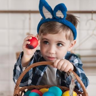Adorable petit garçon tenant un panier avec des oeufs de pâques