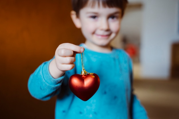 Adorable petit garçon tenant avec un sourire joyeux un coeur en forme de rouge sur son salon