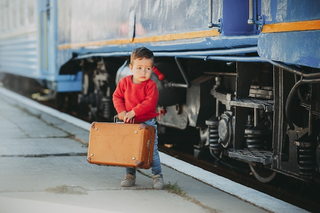 Adorable petit garçon vêtu d'un pull rouge sur une gare près du train avec une vieille valise marron rétro. prêt pour les vacances. jeune voyageur sur la plate-forme.