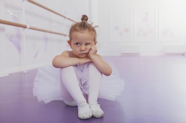 Adorable petite ballerine fille à l'air grincheux, assis seul sur le sol à l'école de ballet