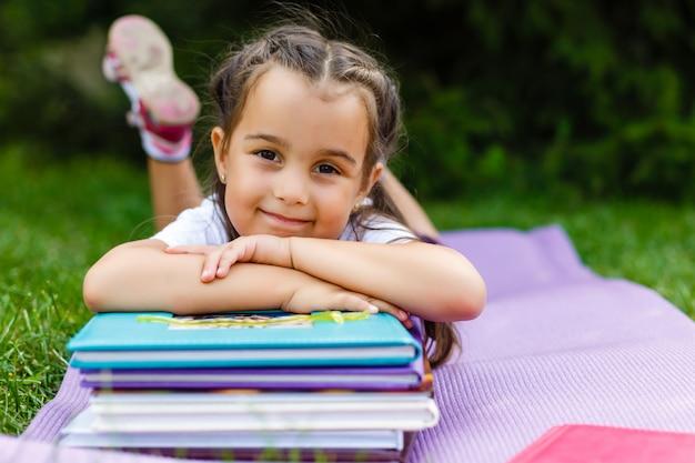 Adorable petite écolière dans un parc de la ville par une belle journée d'automne. education pour les jeunes enfants. retour au concept d'école.