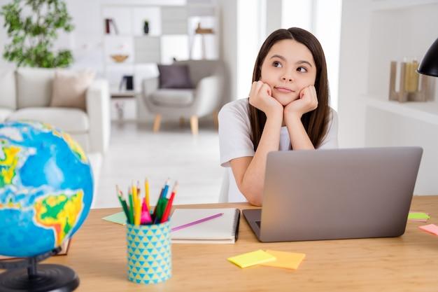 Adorable petite écolière étude à distance à la maison ordinateur portable virtuel apprentissage