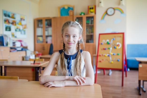 Adorable petite écolière avec des notes et des crayons en plein air.