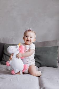 Adorable petite femme joue avec la licorne jouet sur le lit à la maison. concept de journée de l'enfance. bébé heureux, fête de la famille