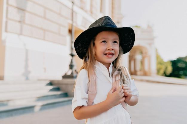 Adorable petite fille adorable au chapeau explorant la ville