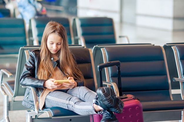 Adorable petite fille à l'aéroport de grand aéroport international près de la fenêtre