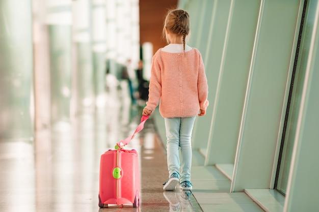 Adorable petite fille à l'aéroport avec ses bagages en attente d'embarquement