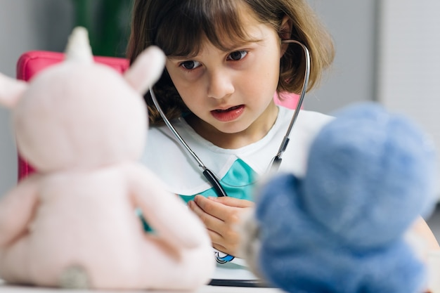 Adorable petite fille d'âge préscolaire mignonne portant un uniforme médical tenant un stéthoscope écoutant un patient jouet malade